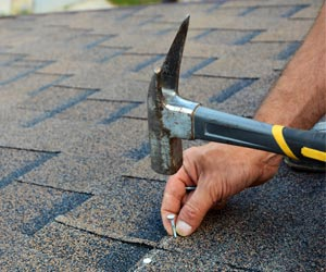 Worker Installing Roof Shingles With Hammer